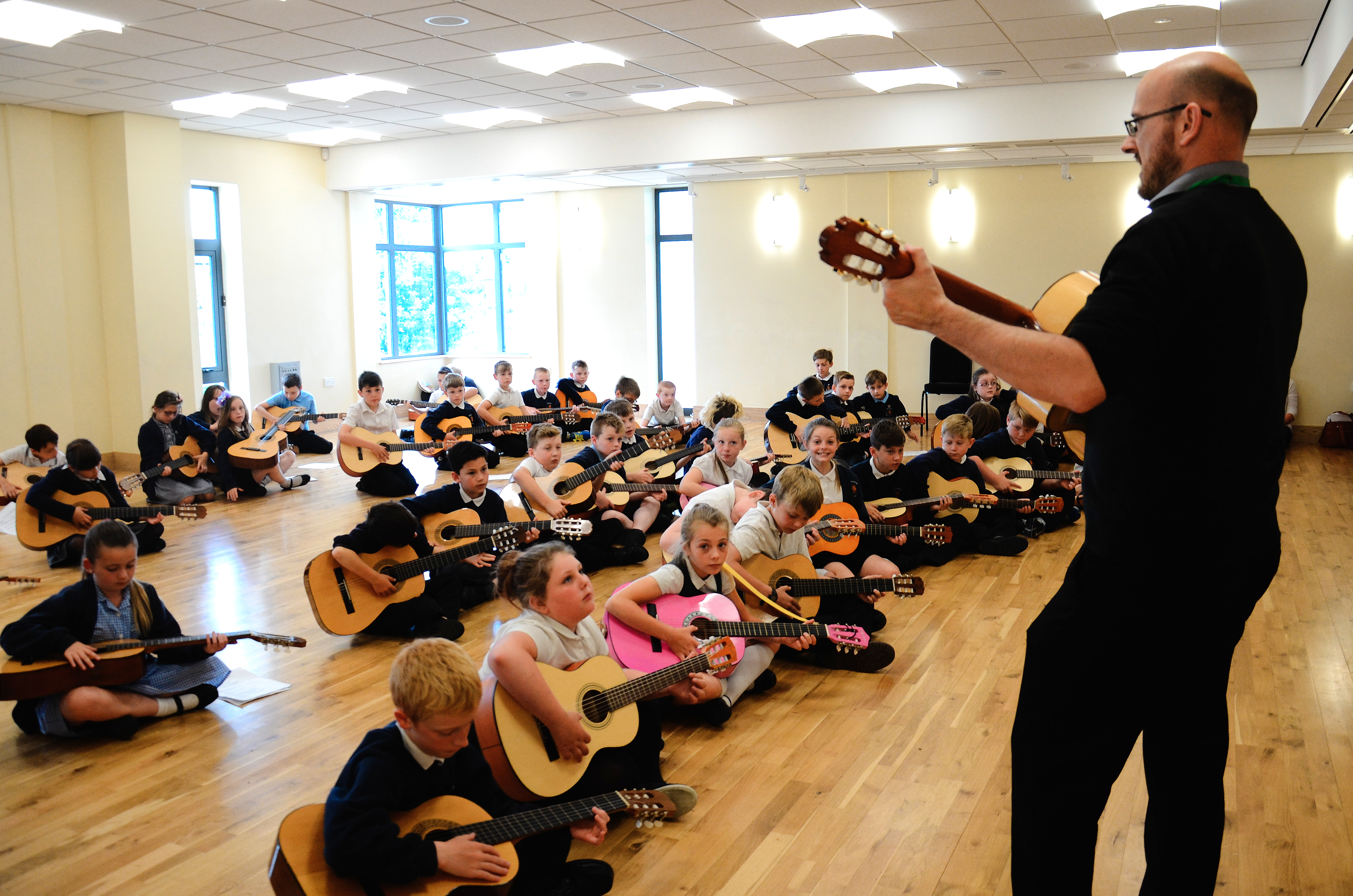 photo of guitar teacher teaching a whole class of students with guitars