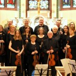 photo of lindsey chamber orchestra after a concert holding their instruments