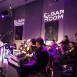 photo of a big band performing in a club with purple light