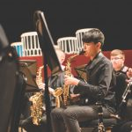 photo of student playing the saxophone during an evening concert