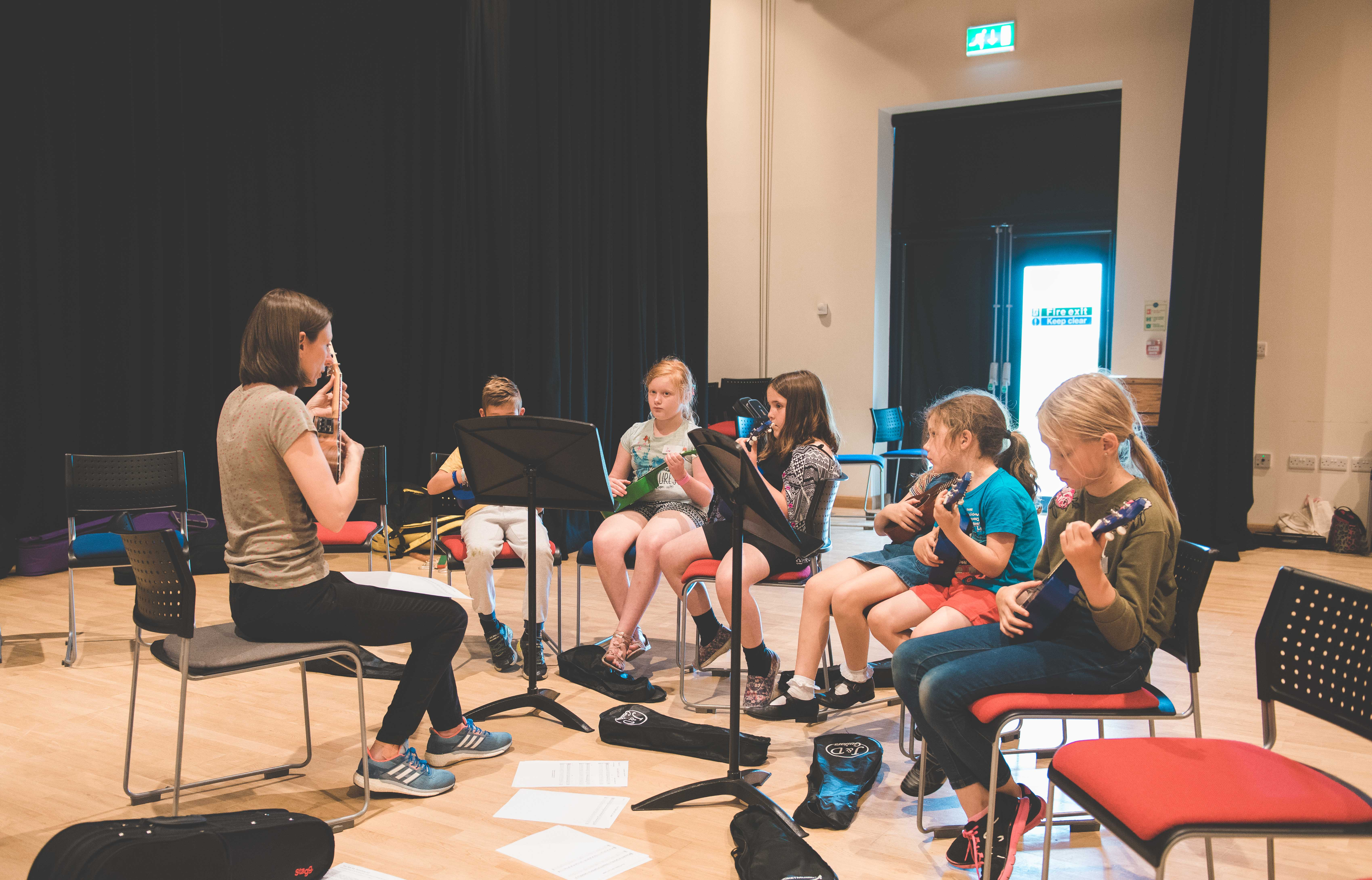 a group of students practising the Ukulele