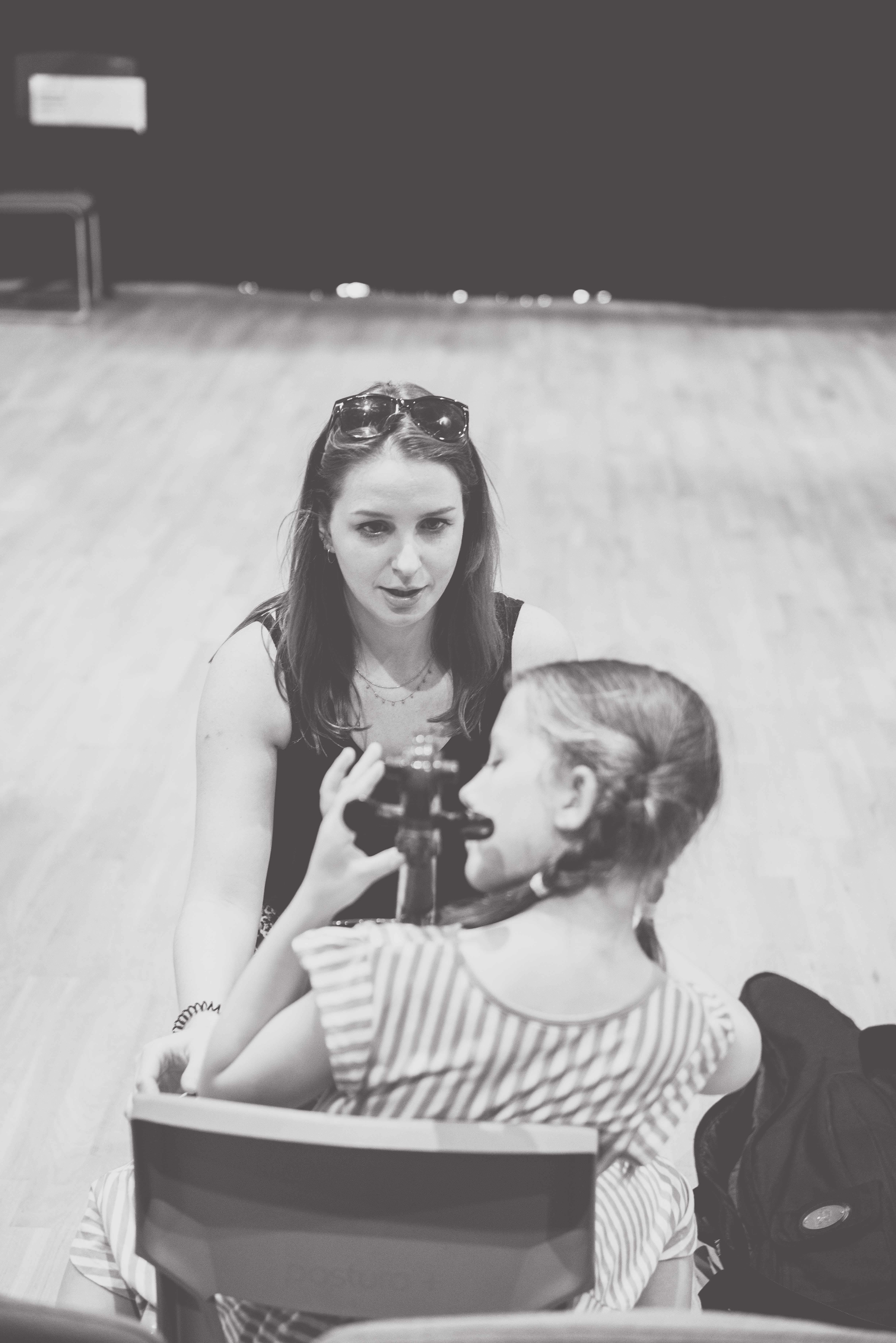 black and white photo of teacher showing a student a new note on the cello