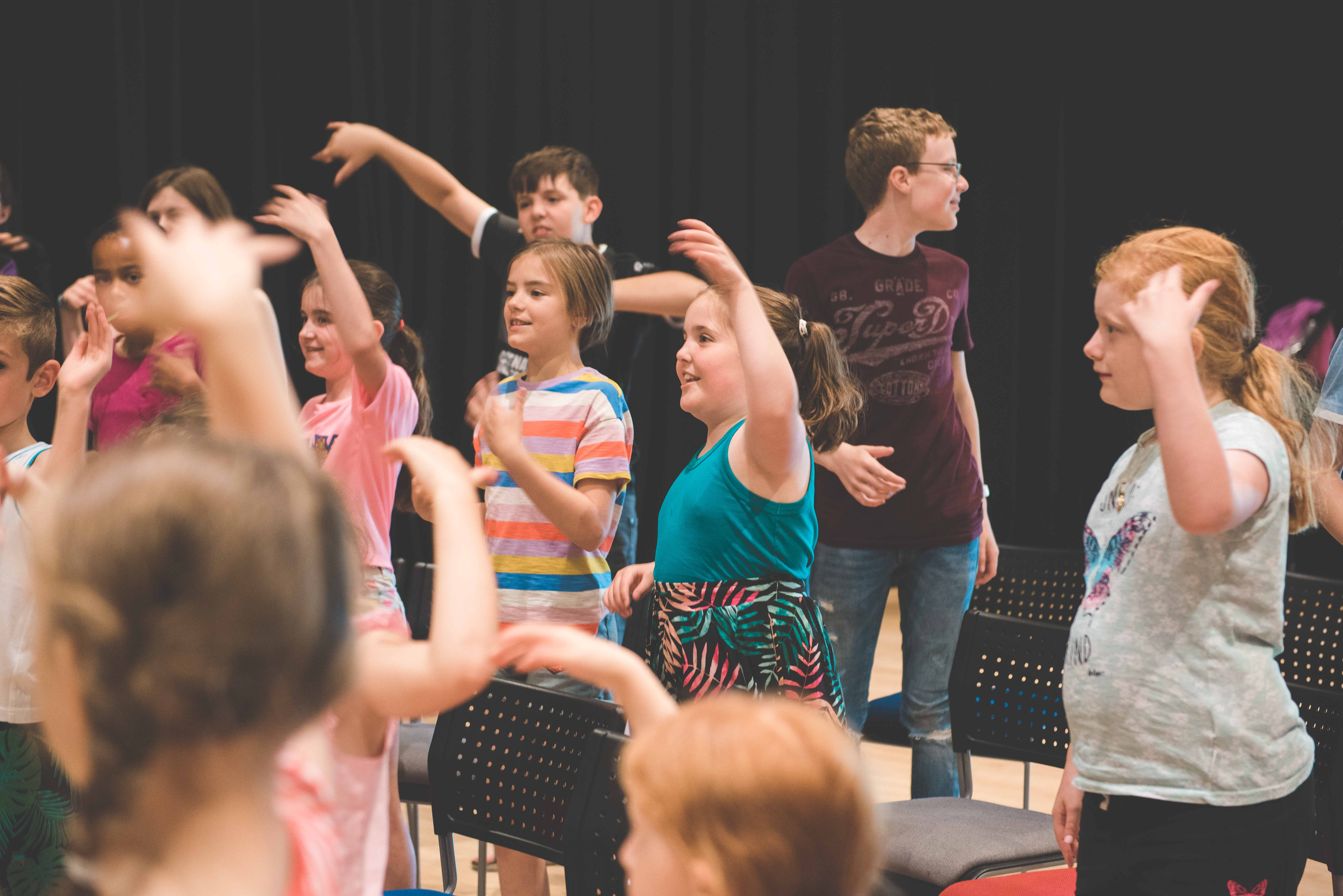 photo of students dancing waving their arms in the air