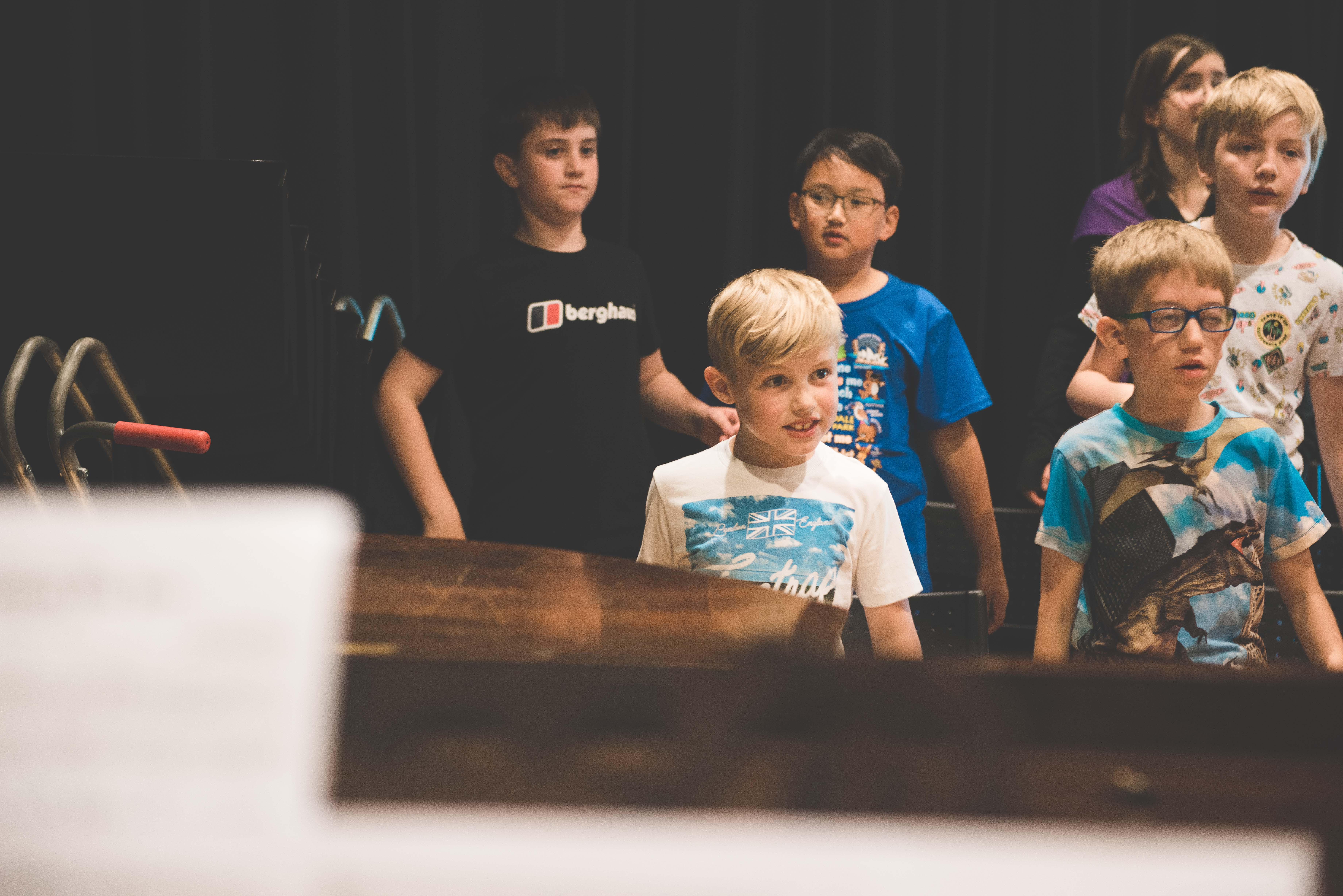photo of young boy amoing group singing with a smile
