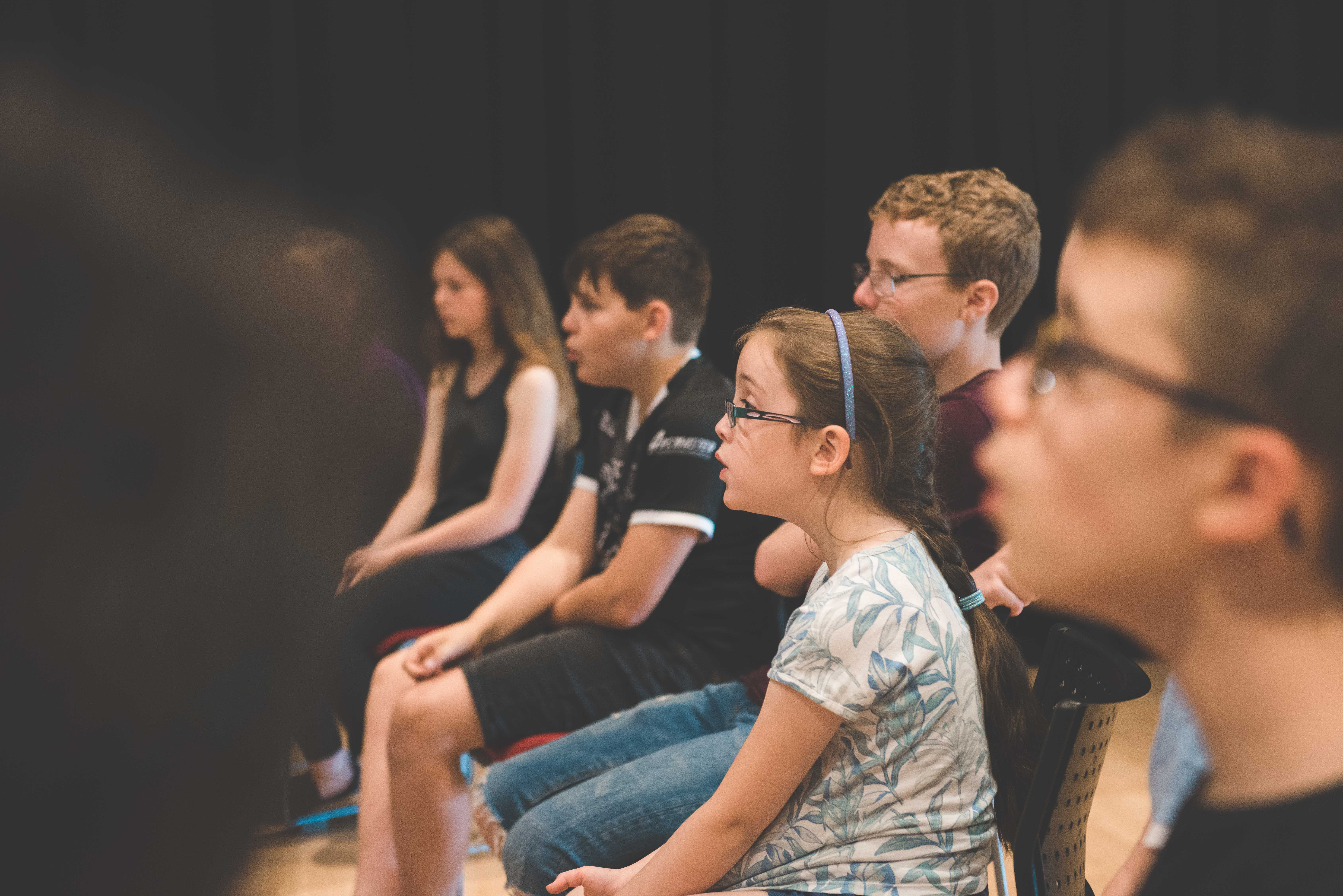 photo of students sat whilst learning a new song