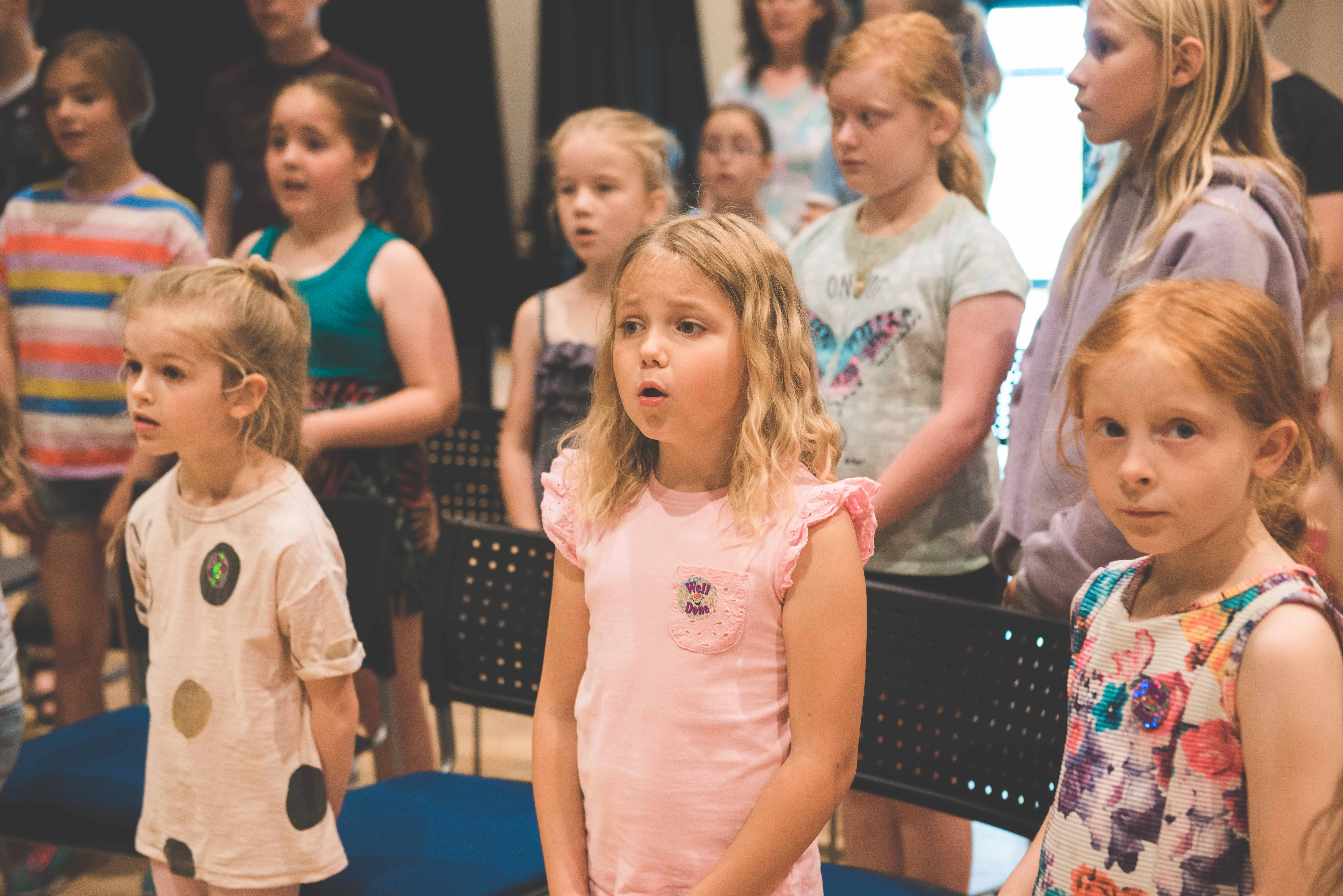 photo of young girl singing in the middle of a group of students