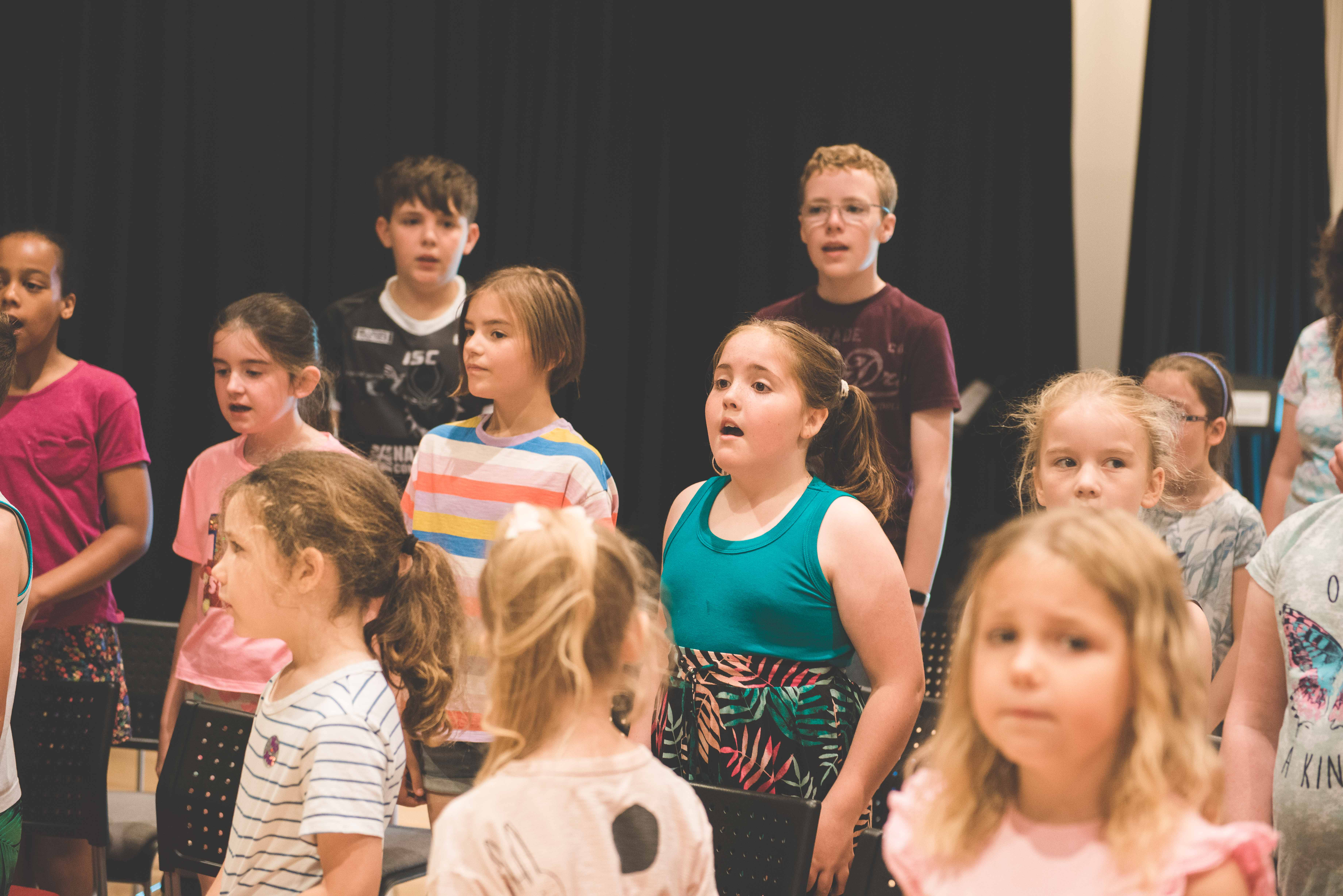 photo of group of young students singing focussing on young girl singing enthusiastically