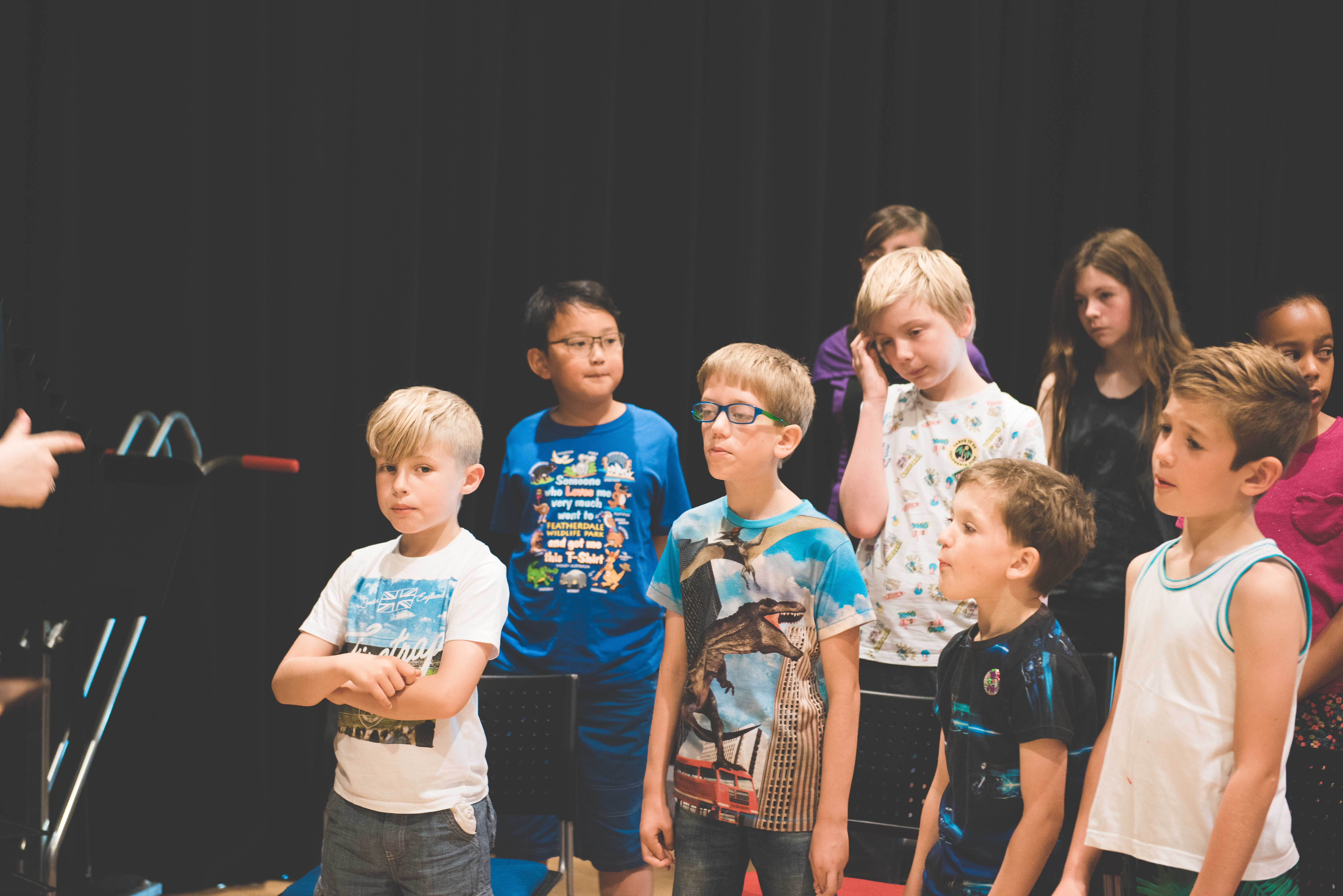 group of boys stood up learning a new song to sing