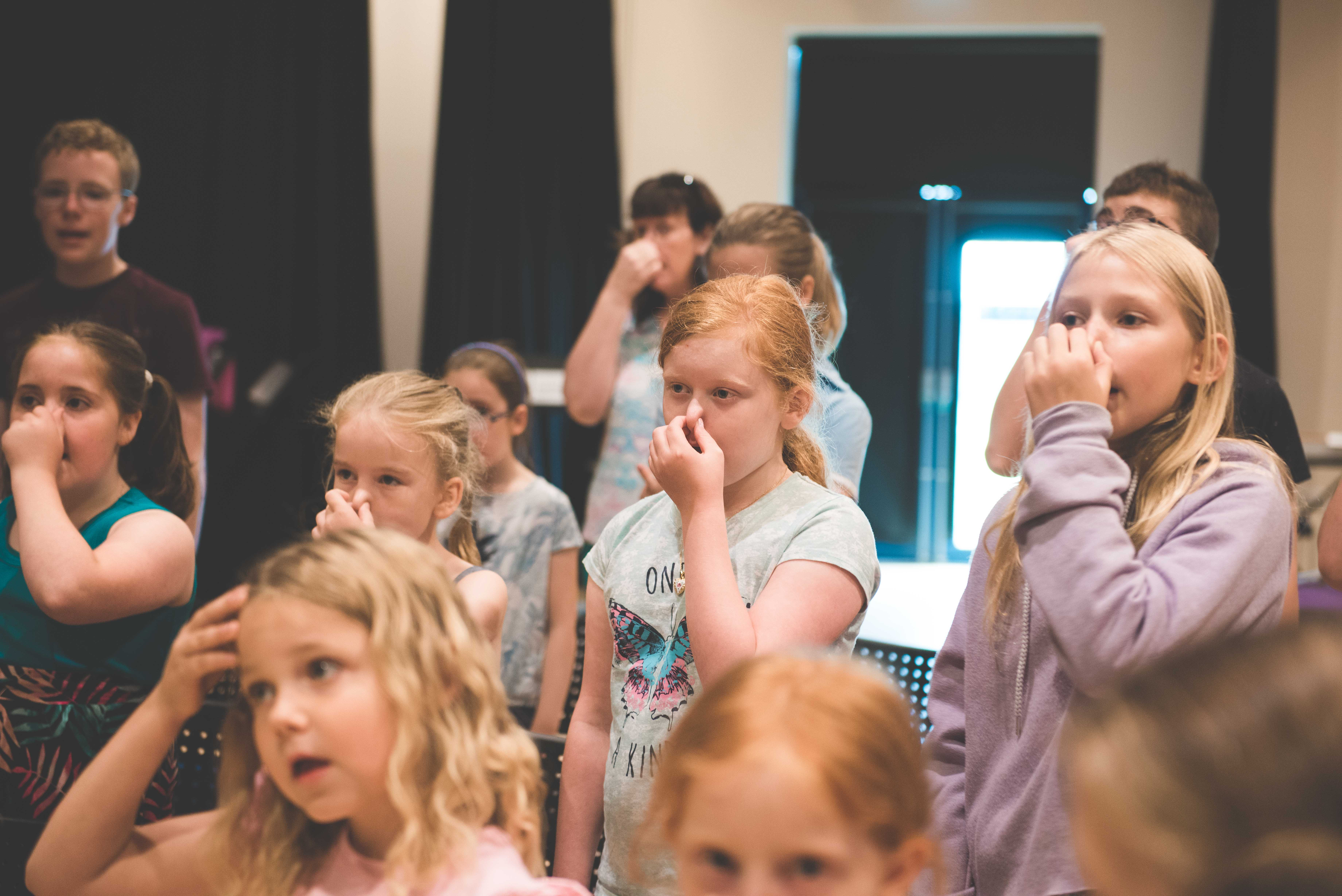 group of students doing some singing techniques holding their noses