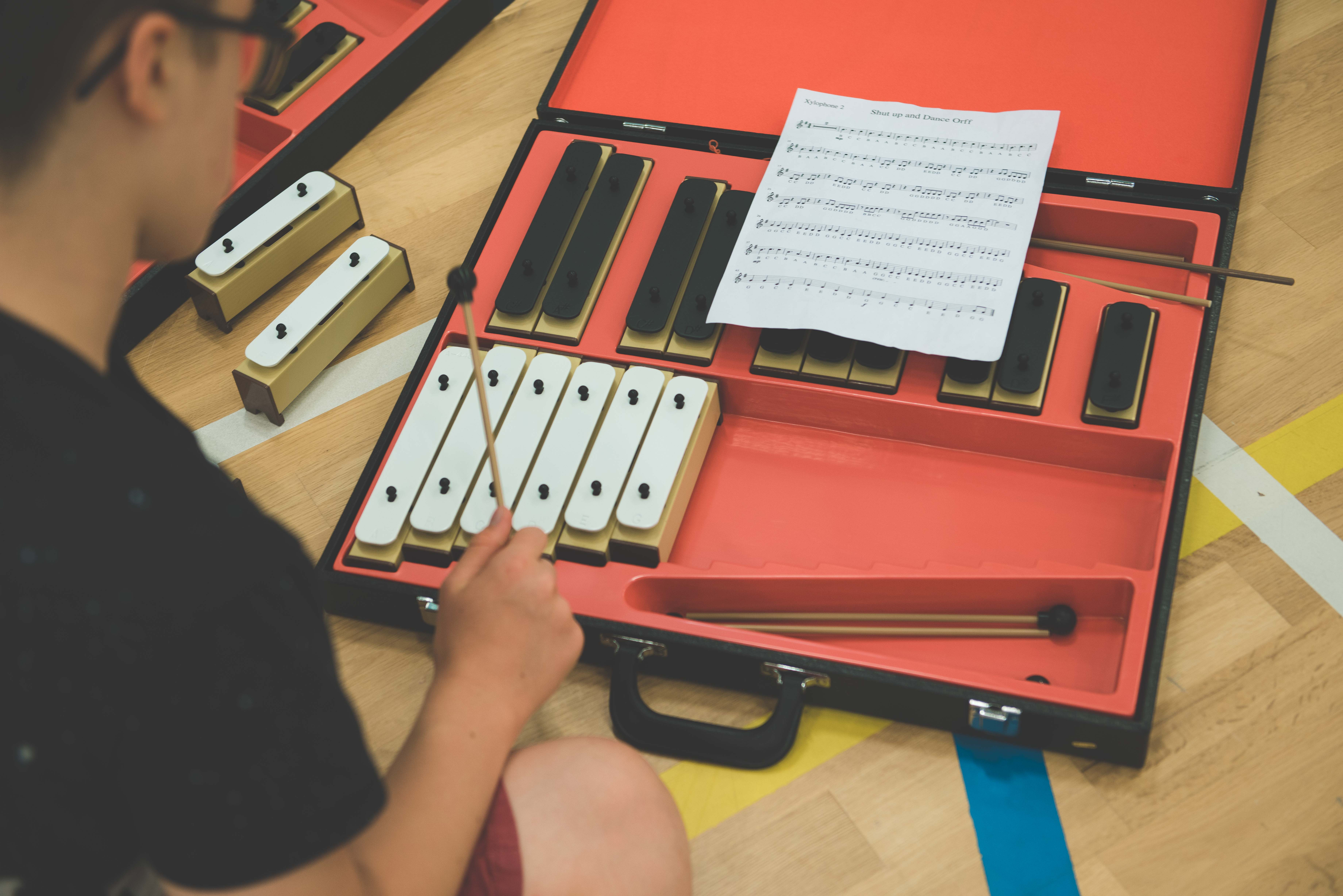 a photo from above of a xylophone and hand of a student playing