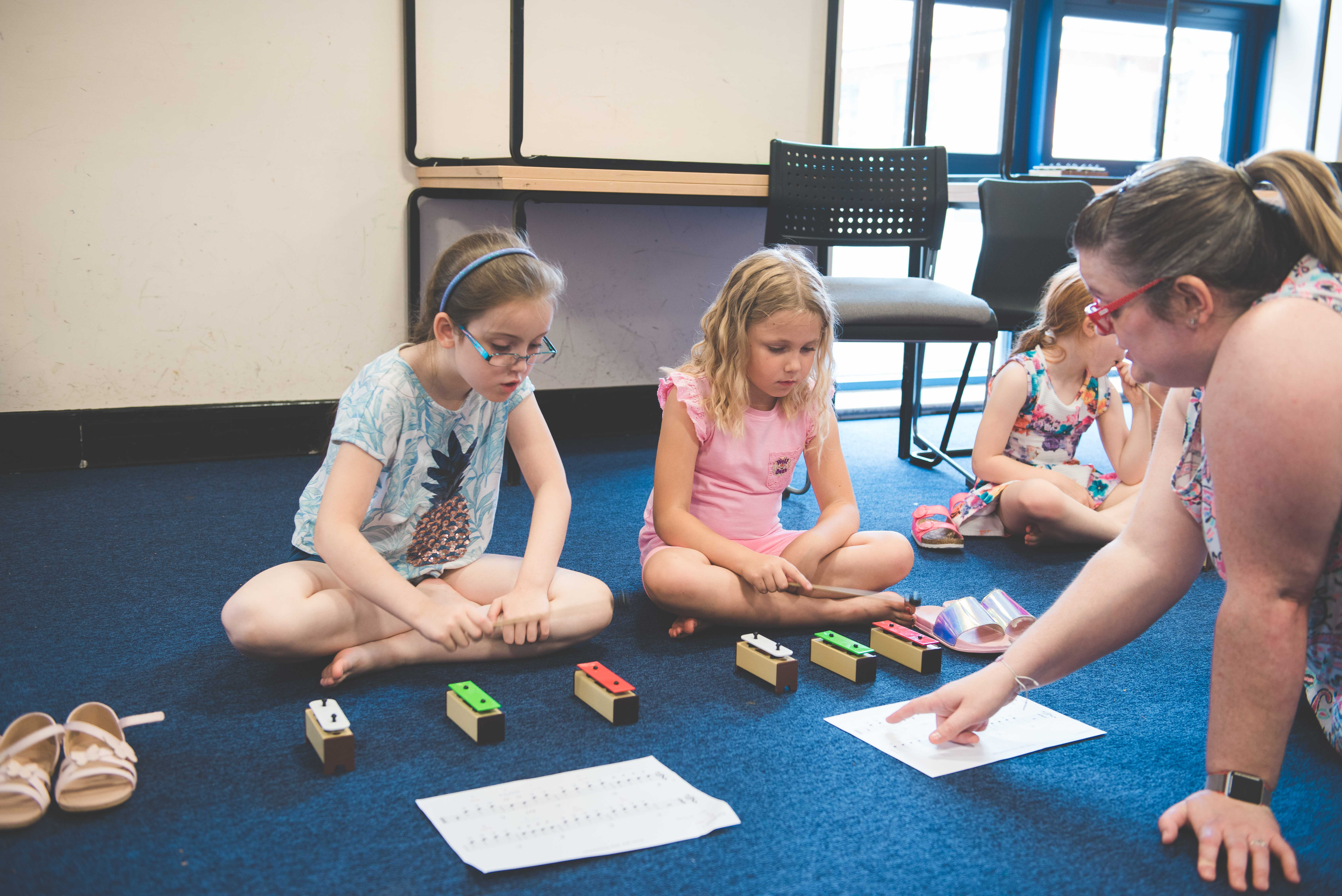 two young girls learning three notes on the xylophone