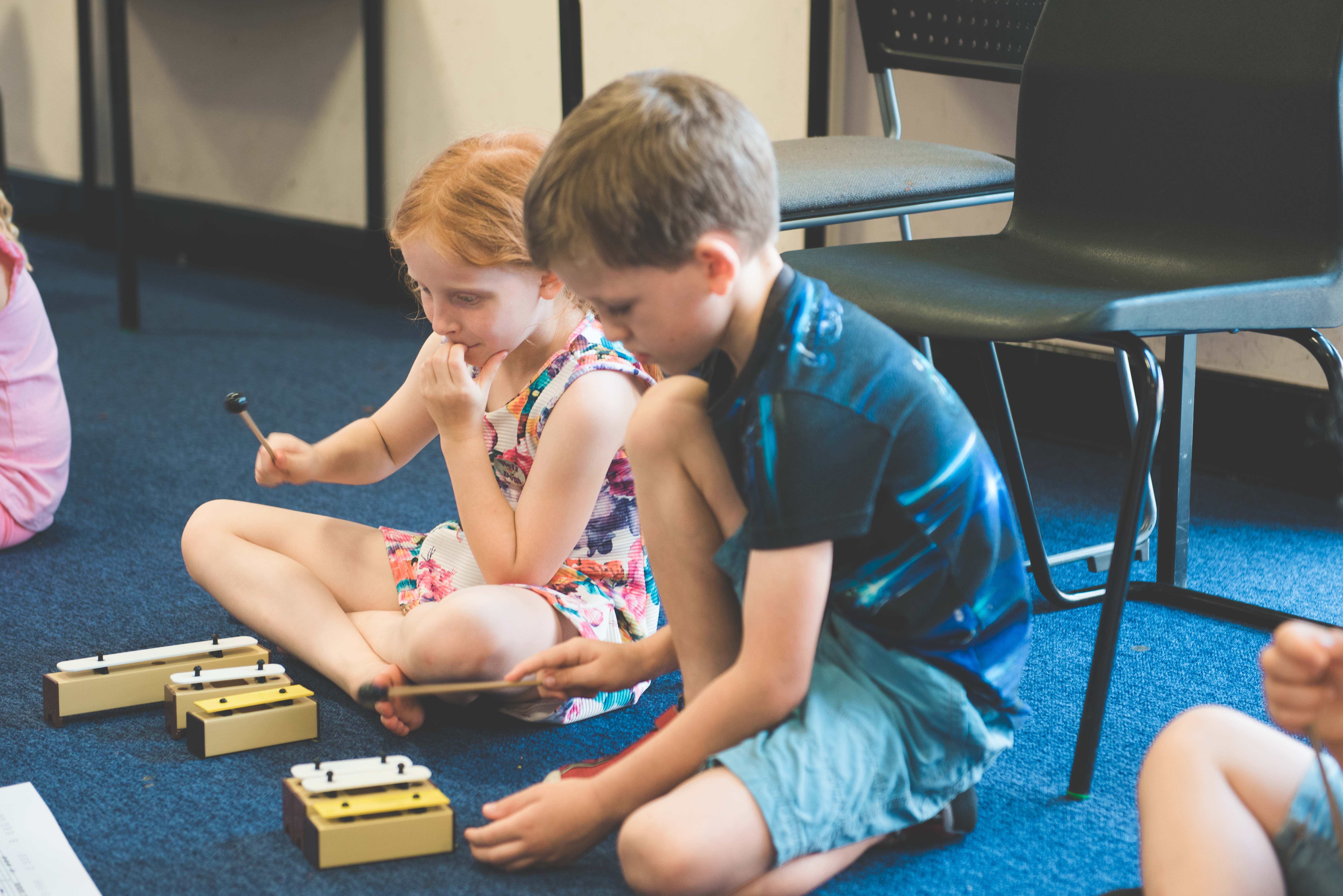 a young boy and girl learning a small xylophone