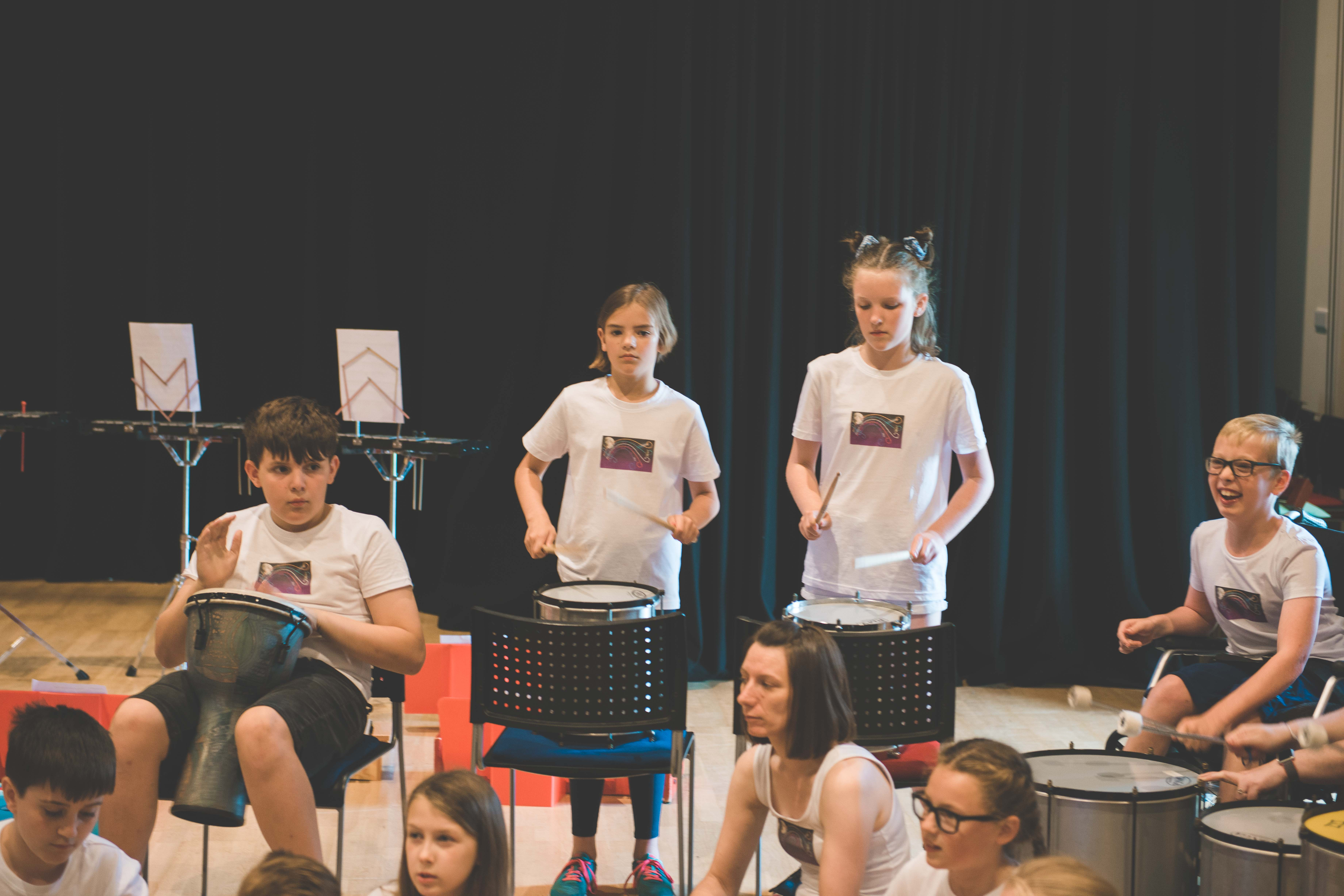 two young girls performing on tom tom drums