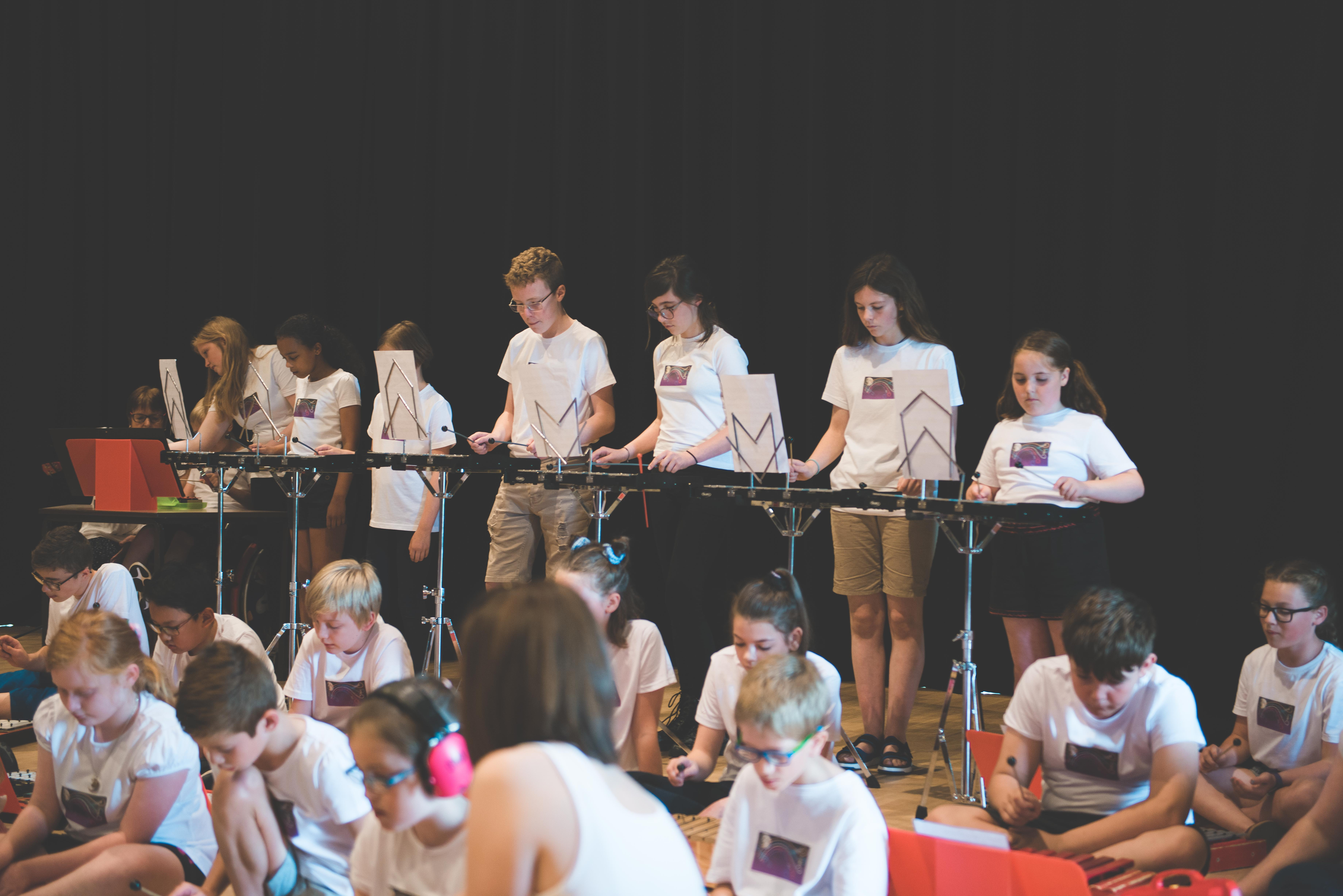 group of sumer school students performing a piece on xylophones
