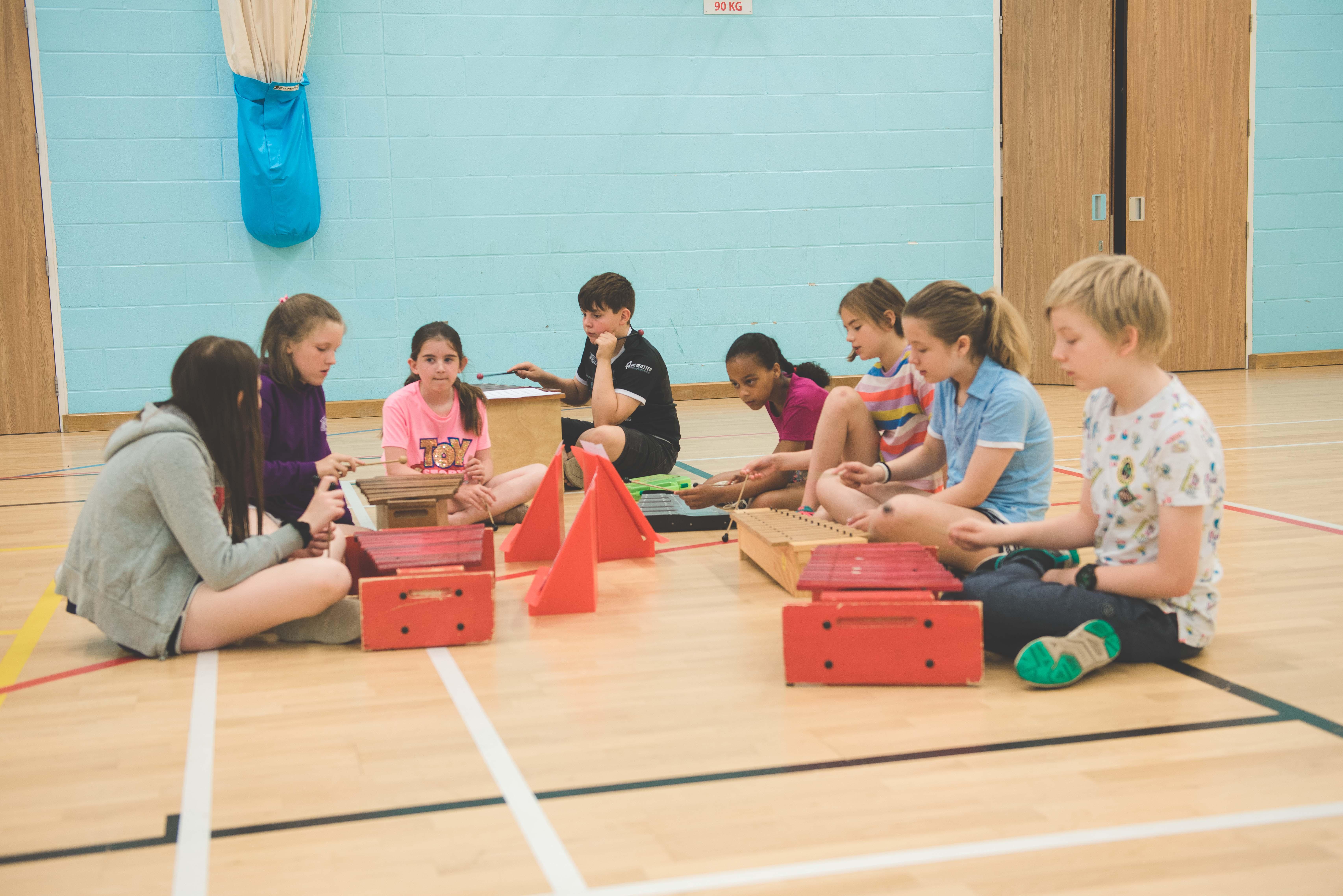 group of 7 summer school students practising xylophone